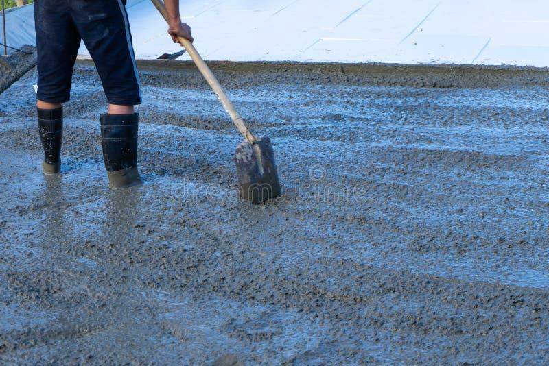 Arbeitskräfte gießen die Grundlage für den Bau eines Wohngebäudes unter Verwendung der mobilen Mischer stockbild