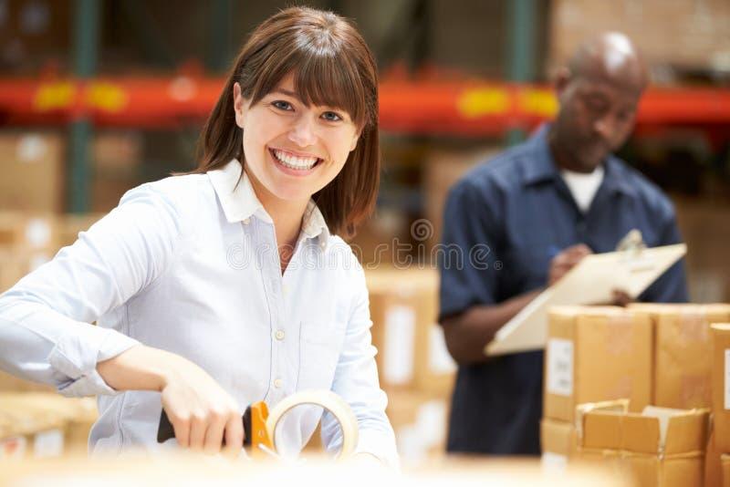 Arbeitskräfte im Lager, das Waren für Versand vorbereitet stockfoto