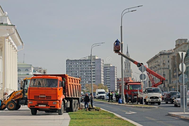 Arbeitskräfte legen einen Rasen und produzieren elektrische Installation auf einem Laternenpfahl in Moskau stockbild