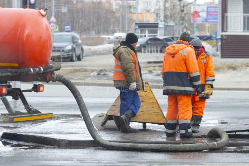 Arbeitskräfte pumpten heraus den Abwasserkanal nahe der Straße durch die Luke mithilfe zwei fachkundiger Autos lizenzfreie stockfotografie