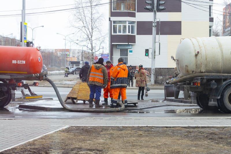 Arbeitskräfte pumpten heraus den Abwasserkanal nahe der Straße durch die Luke mithilfe zwei fachkundiger Autos stockfotos