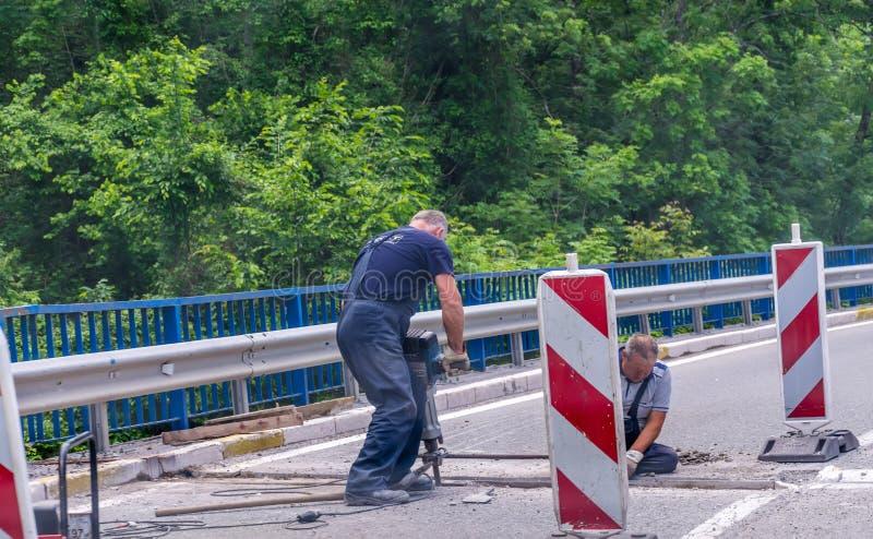 Arbeitskräfte stellen die Straße nahe dem Kloster von Moraca wieder her stockbild