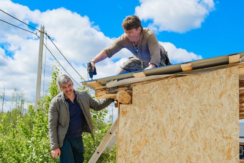 Arbeitskräfte stellen ein Dach in einem Landhaus her lizenzfreie stockfotografie
