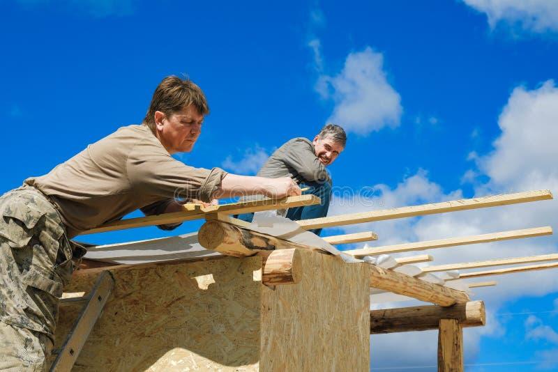 Arbeitskräfte stellen ein Dach in einem Landhaus her lizenzfreie stockbilder