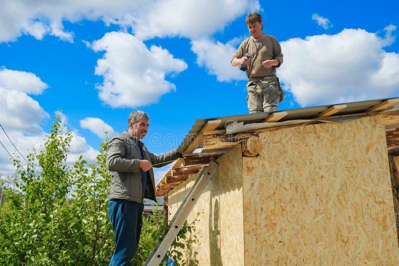 Arbeitskräfte stellen ein Dach in einem Landhaus her lizenzfreie stockfotos