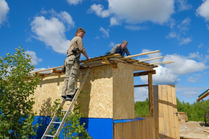 Arbeitskräfte stellen ein Dach in einem Landhaus her lizenzfreies stockfoto