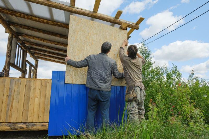 Arbeitskräfte stellen ein Dach in einem Landhaus her stockfoto