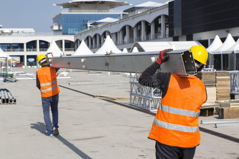 Arbeitskräfte tragen Baumetallrohre lizenzfreie stockfotos