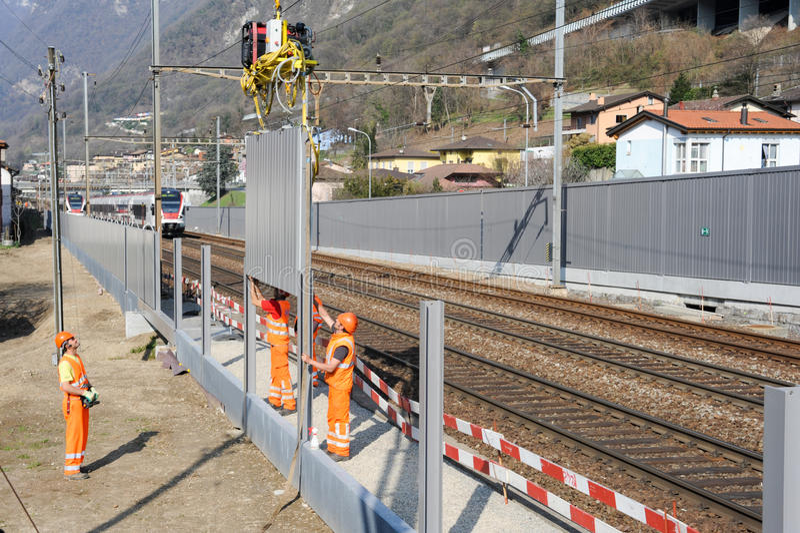 Arbeitskräfte während der Installation der Geräuschsperren auf der Eisenbahn stockfotografie