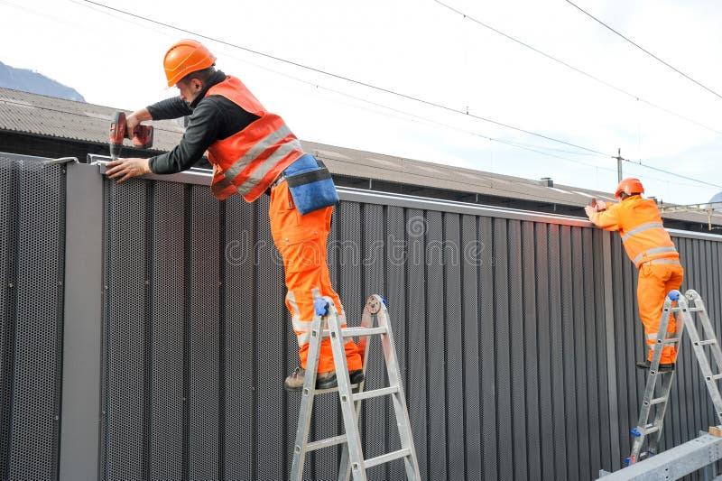 Arbeitskräfte während der Installation der Geräuschsperren auf der Eisenbahn lizenzfreie stockfotografie