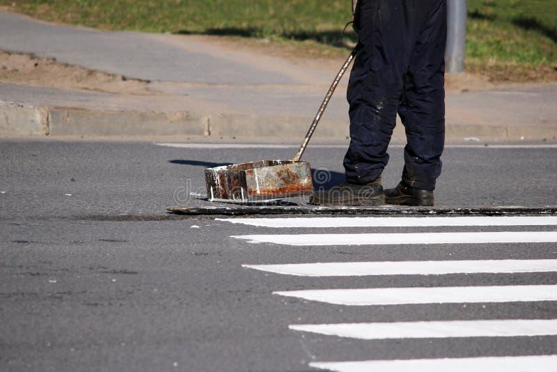 Arbeitskräfte wenden eine Fahrbahnmarkierung am Fußgängerübergangzebrastreifenzebrastreifen mit weißer Farbe an und besprühen die lizenzfreies stockfoto
