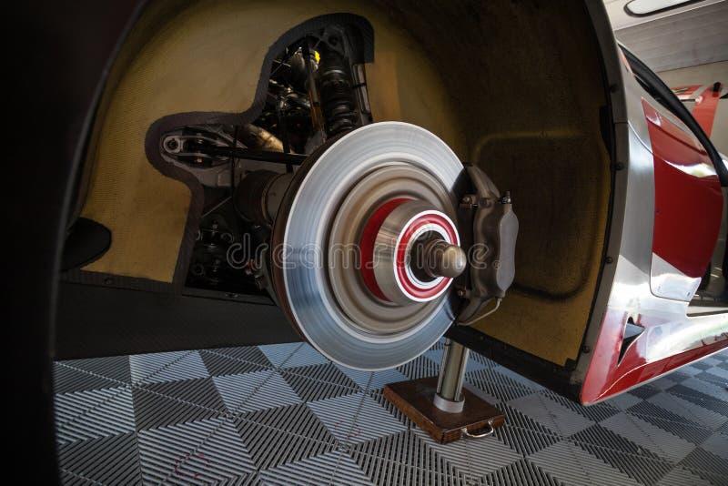 Arbeitskr?fte ?berpr?fen die hinteren Bremsen eines Supercar in der Garage lizenzfreie abbildung