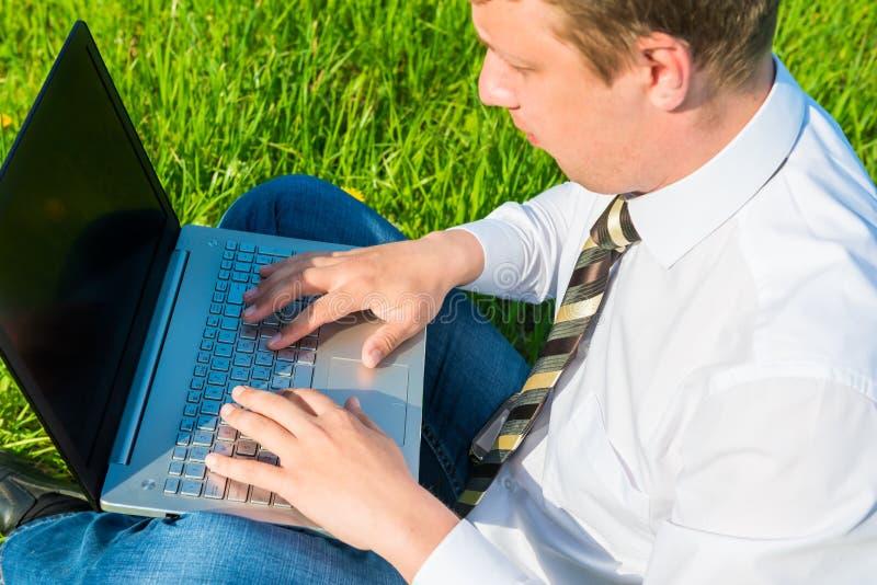 Arbeitskraft arbeitet an dem Rasen mit Laptop stockbilder