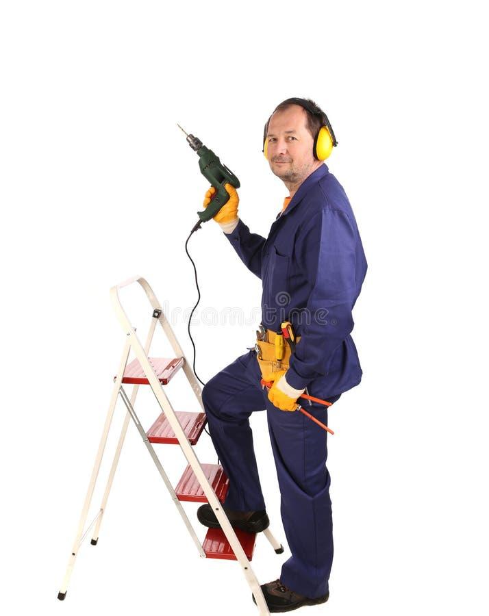 Arbeitskraft auf Leiter mit Bohrgerät. lizenzfreie stockfotos