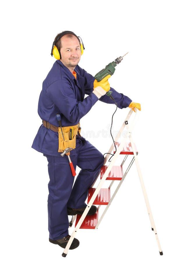 Arbeitskraft auf Leiter mit Bohrgerät stockbilder