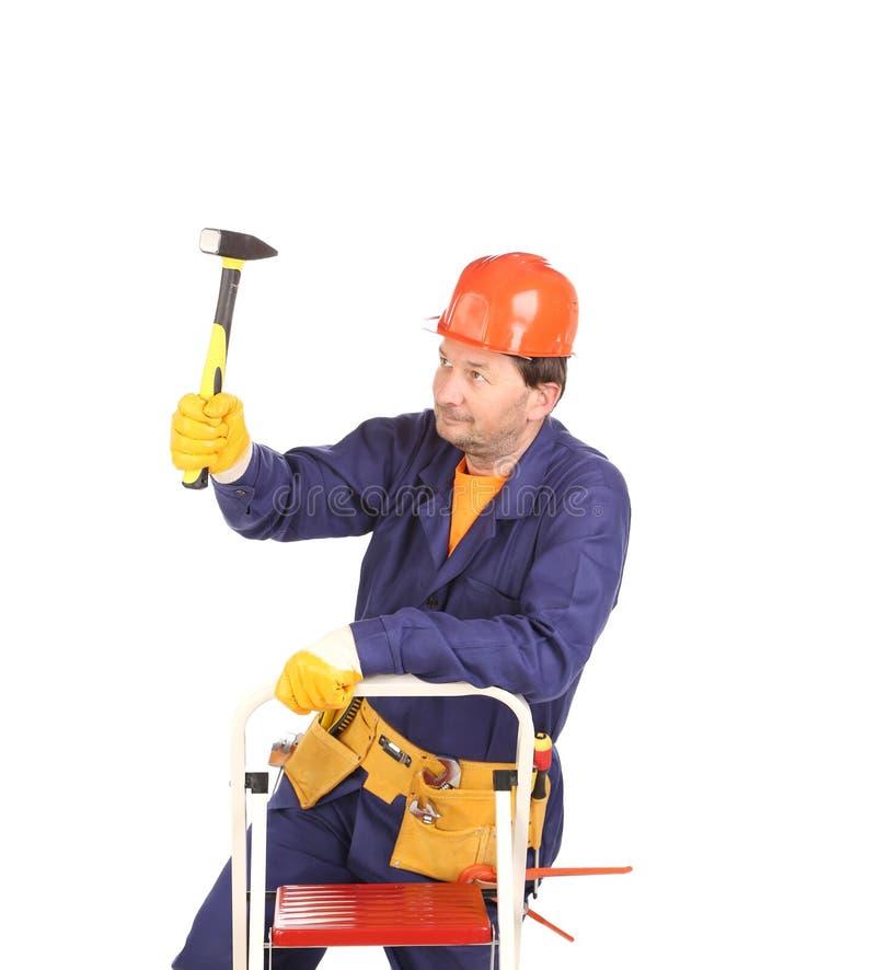 Arbeitskraft auf Leiter mit Hammer stockfotografie