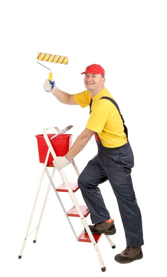 Arbeitskraft auf Leiter mit Rolle und Eimer lizenzfreies stockbild