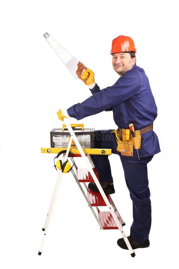 Arbeitskraft auf Leiter mit sah lizenzfreie stockfotografie