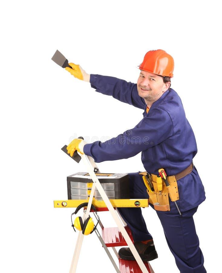 Arbeitskraft auf Leiter mit Spachtel lizenzfreies stockfoto