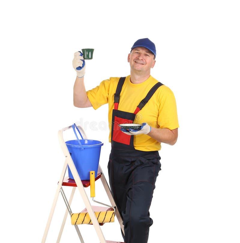 Arbeitskraft auf Leiter mit Tasse Tee. stockbilder