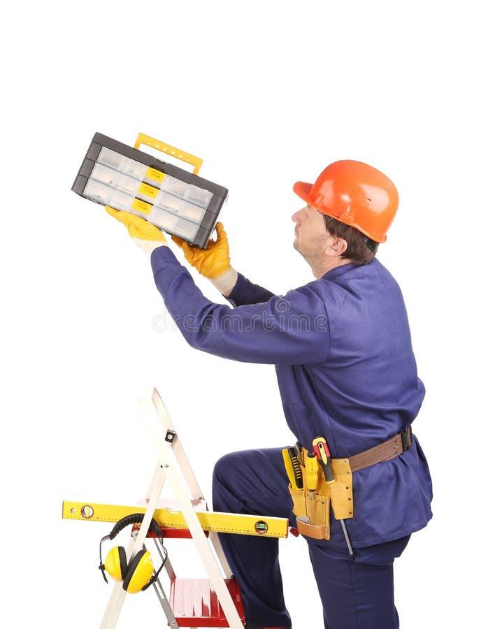 Arbeitskraft auf Leiter mit Werkzeugkasten lizenzfreie stockbilder