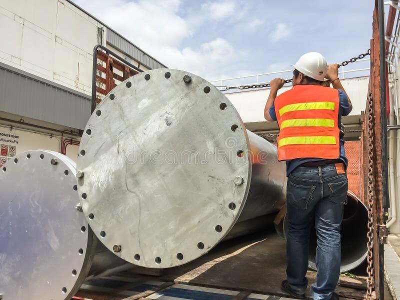 Arbeitskraft auf LKW mit großem Metallrohr, der Mannabnutzung Warnkleidung und Schutzhelm, Auftragnehmerjob stockfotografie