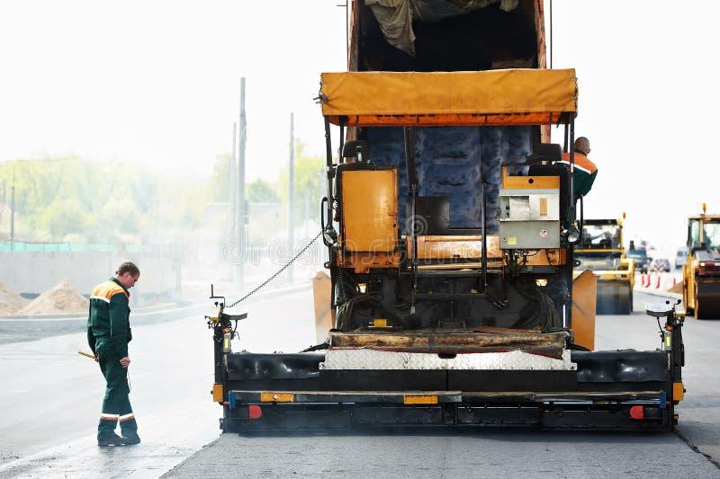 Arbeitskraft bei den asphaltierenarbeiten stockfotos