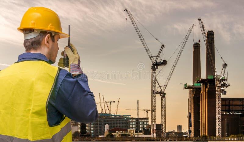 Arbeitskraft benutzt Radio- und Kranstandort Goldtasten in den Fingern mit Häusern stockfoto