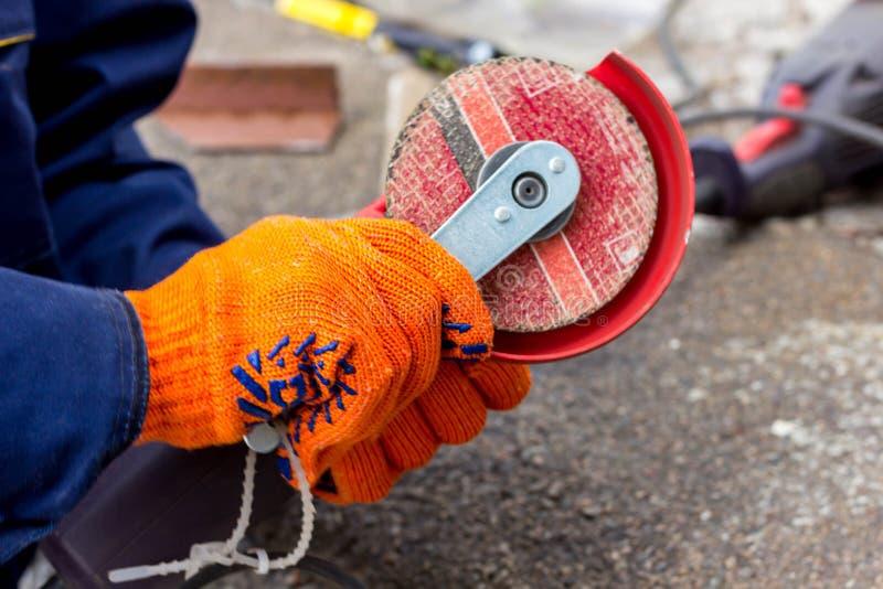 Arbeitskraft benutzt Winkel-Antriebsschleifer für Arbeit Wie man im Winkel-Antriebsschleifer eine Arbeitsscheibe ersetzt lizenzfreie stockfotografie