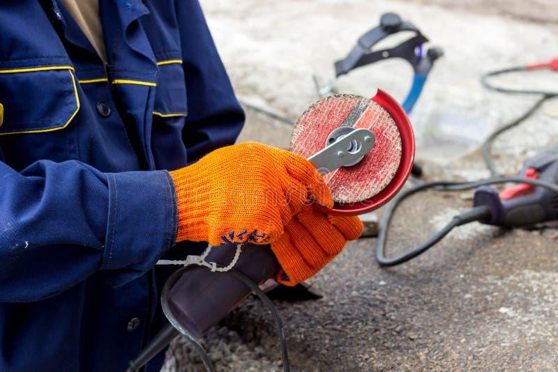 Arbeitskraft benutzt Winkel-Antriebsschleifer für Arbeit Wie man im Winkel-Antriebsschleifer eine Arbeitsscheibe ersetzt stockfoto