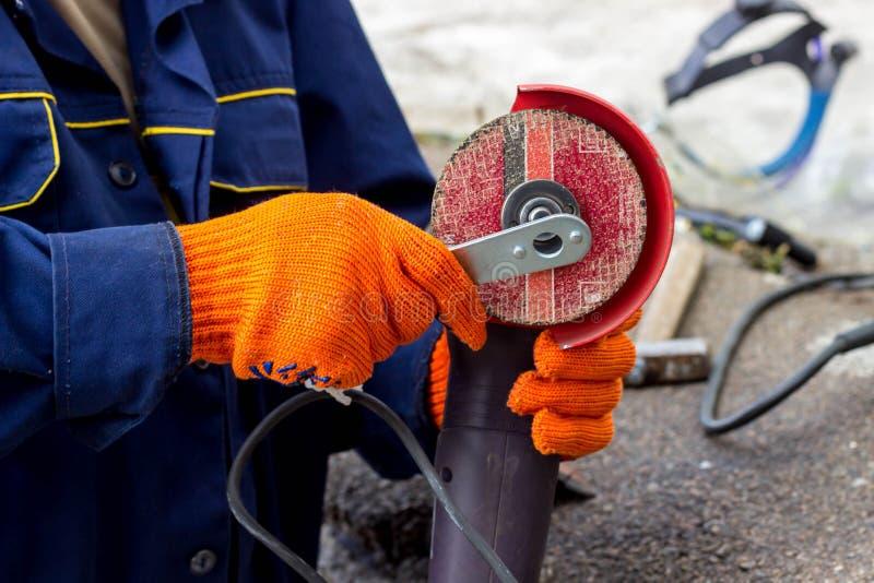 Arbeitskraft benutzt Winkel-Antriebsschleifer für Arbeit Wie man im Winkel-Antriebsschleifer eine Arbeitsscheibe ersetzt stockfotografie