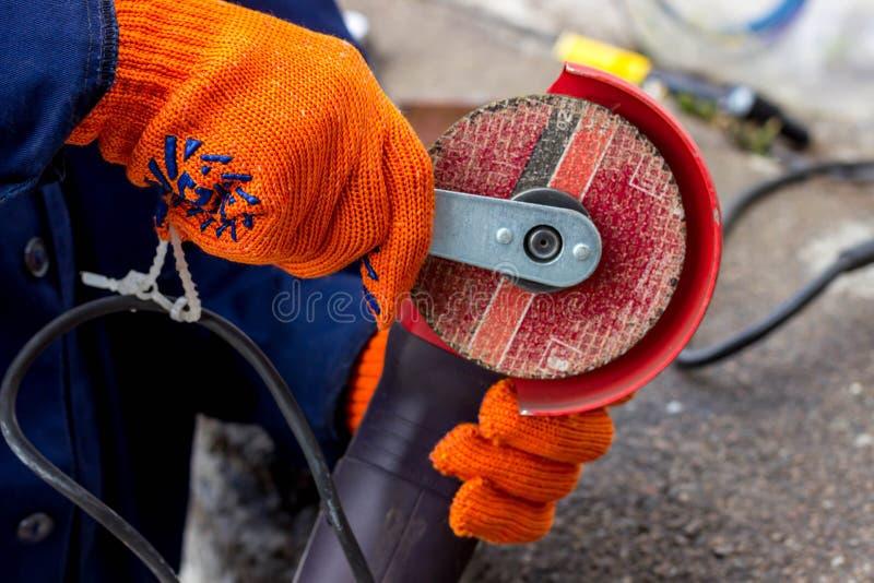 Arbeitskraft benutzt Winkel-Antriebsschleifer für Arbeit Wie man im Winkel-Antriebsschleifer eine Arbeitsscheibe ersetzt lizenzfreie stockfotos
