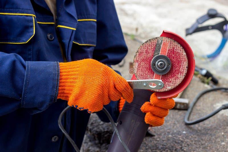 Arbeitskraft benutzt Winkel-Antriebsschleifer für Arbeit Wie man im Winkel-Antriebsschleifer eine Arbeitsscheibe ersetzt lizenzfreies stockbild