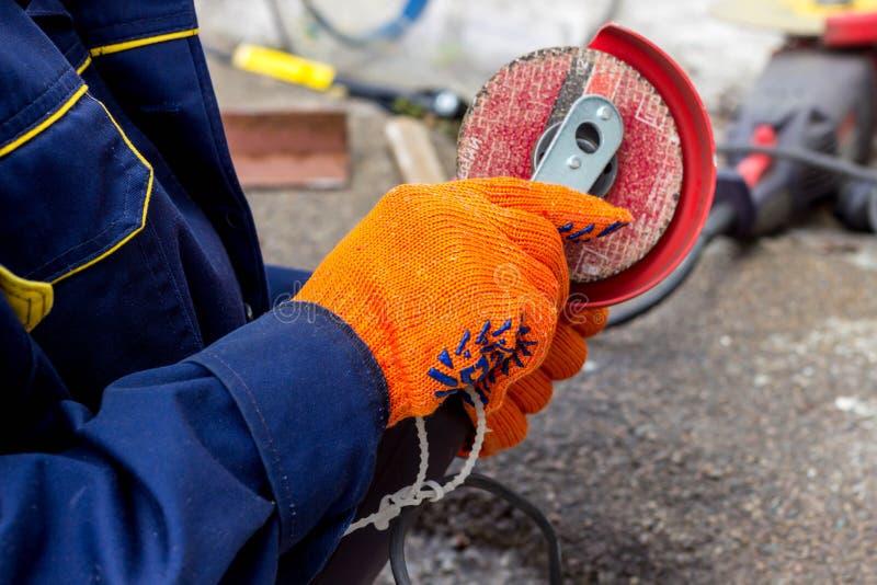 Arbeitskraft benutzt Winkel-Antriebsschleifer für Arbeit Wie man im Winkel-Antriebsschleifer eine Arbeitsscheibe ersetzt stockfotos