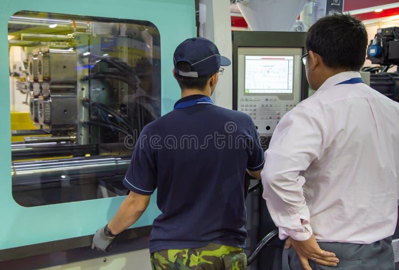 Arbeitskraft betreiben Spritzen-Pressemaschine stockfoto