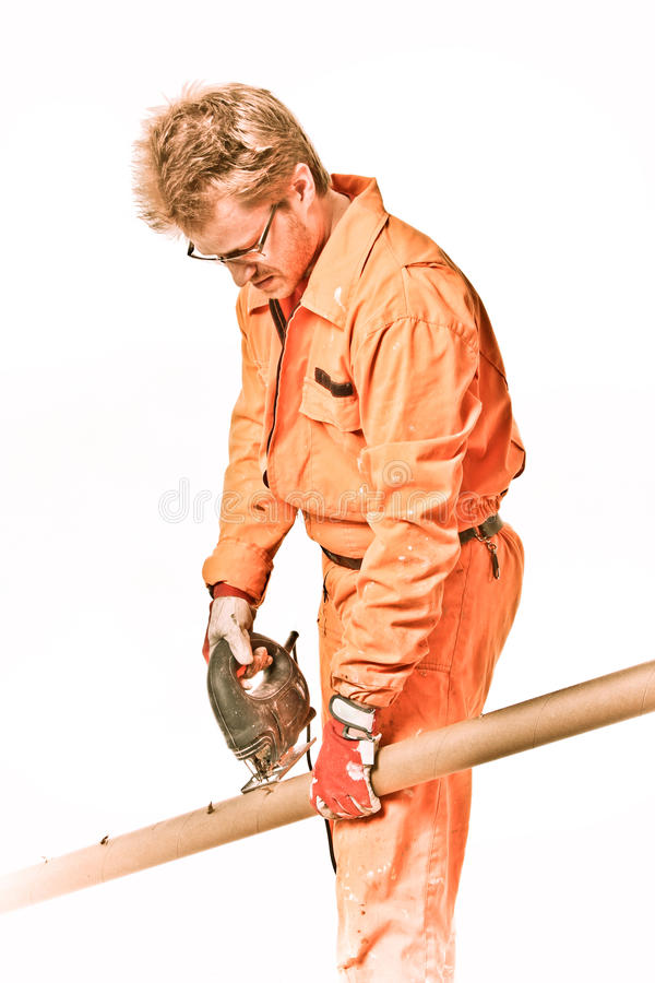 Arbeitskraft in den Gesamten sägt Rohr mit einer Tischlerbandsäge lizenzfreie stockfotografie