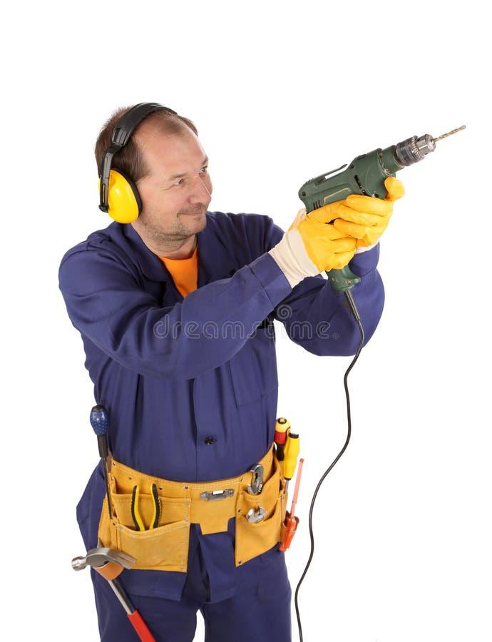 Arbeitskraft in den Kopfhörern mit Bohrgerät. stockfoto