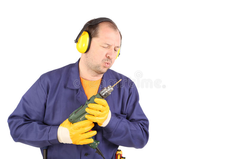 Arbeitskraft in den Ohrmuffen mit Bohrgerät lizenzfreies stockbild