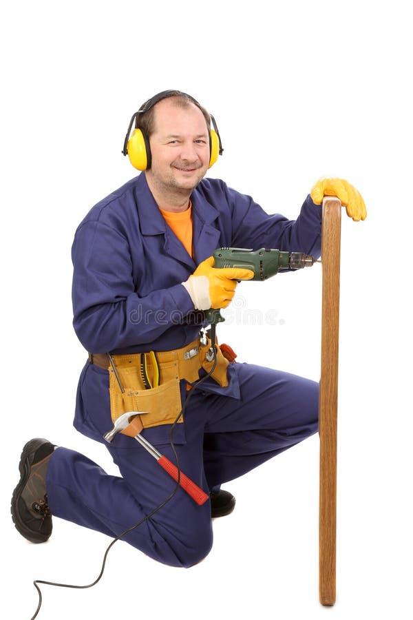 Arbeitskraft in den Ohrmuffen mit Bohrgerät und Brett stockfotos
