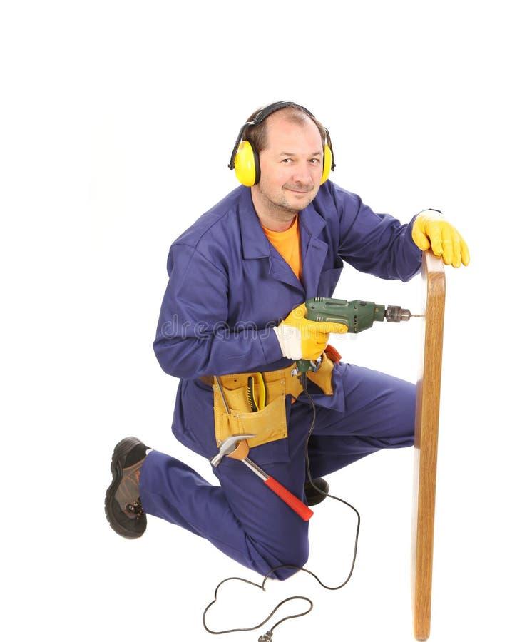 Arbeitskraft in den Ohrmuffen mit Bohrgerät und Brett stockbild