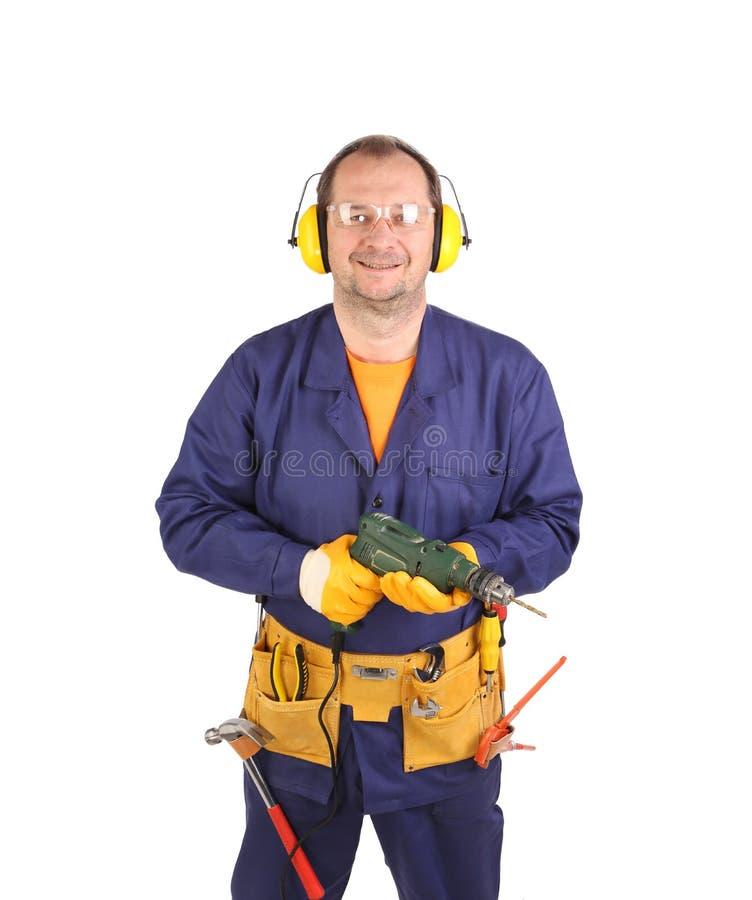 Arbeitskraft in den Ohrmuffen und -gläsern mit Bohrgerät. lizenzfreie stockfotografie