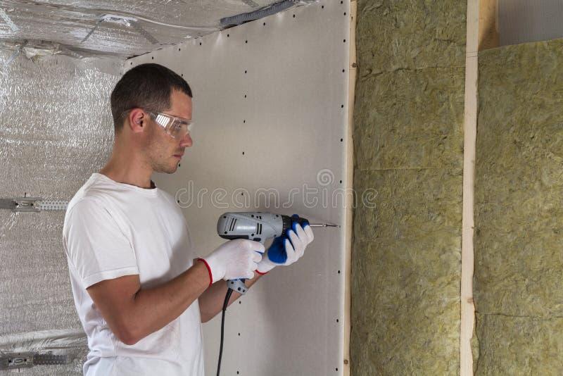 Arbeitskraft in den Schutzbrillen mit dem Schraubenzieher, der an Isolierung arbeitet Drywal lizenzfreies stockfoto