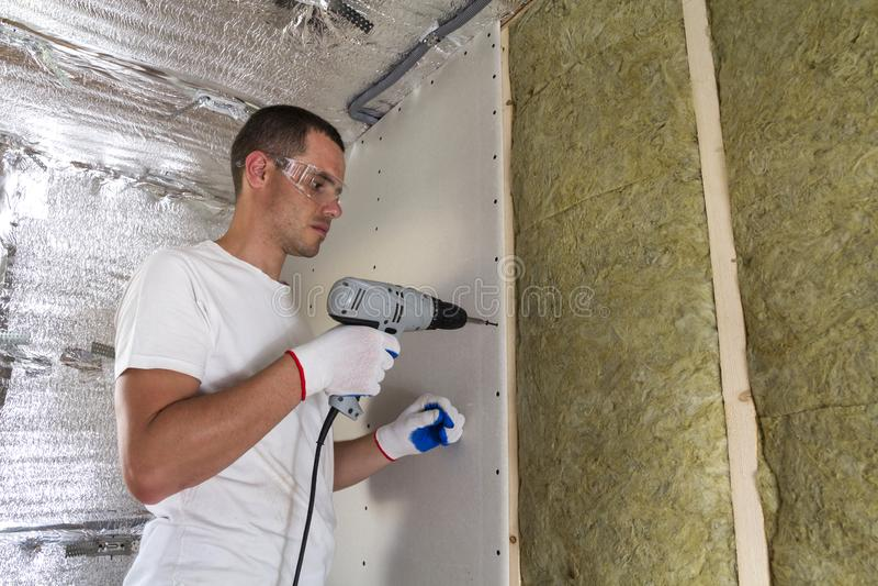 Arbeitskraft in den Schutzbrillen mit dem Schraubenzieher, der an Isolierung arbeitet Drywal lizenzfreie stockfotos