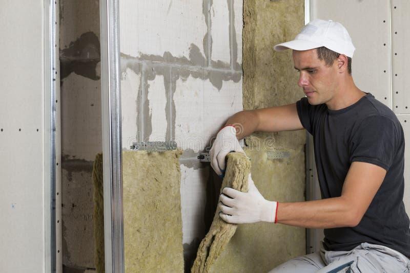 Arbeitskraft in den Schutzhandschuhen, die Steinwolleisolierung in w isolieren lizenzfreie stockfotos