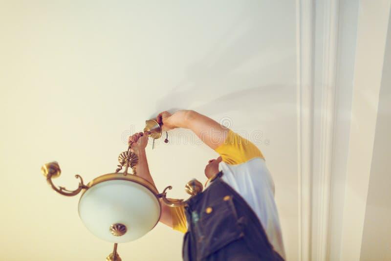 Arbeitskraft in der Arbeitskleidung installiert einen Leuchter und schließt ihn an Strom auf der Decke von der Leiter in der Wohn lizenzfreies stockbild
