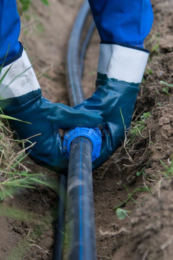 Arbeitskraft in der blauen Uniform, die Wasserleitungen und einen Elektriker in einem Graben legt lizenzfreie stockbilder