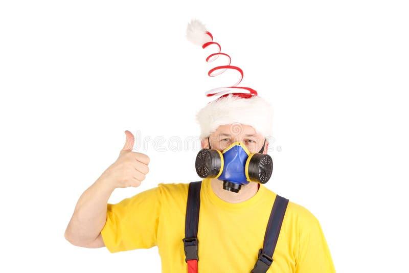 Arbeitskraft in der Gasmaske und im Spaßhut zeigt Daumen stockfoto