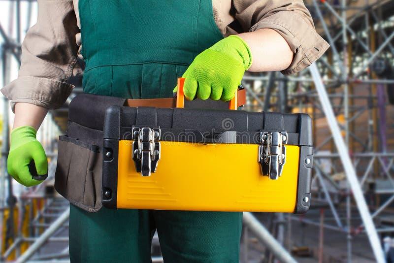 Arbeitskraft in der grünen Gesamtausstattung mit Werkzeugkasten lizenzfreie stockfotos