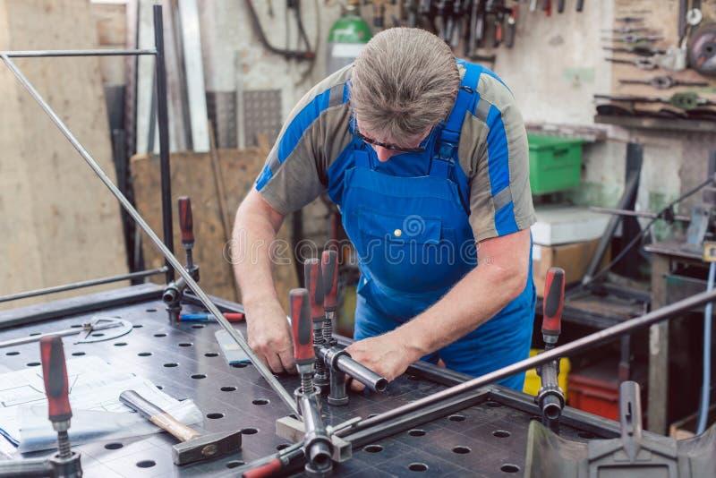 Arbeitskraft in der Metallwerkstatt mit Werkzeugen und Werkstück lizenzfreie stockbilder
