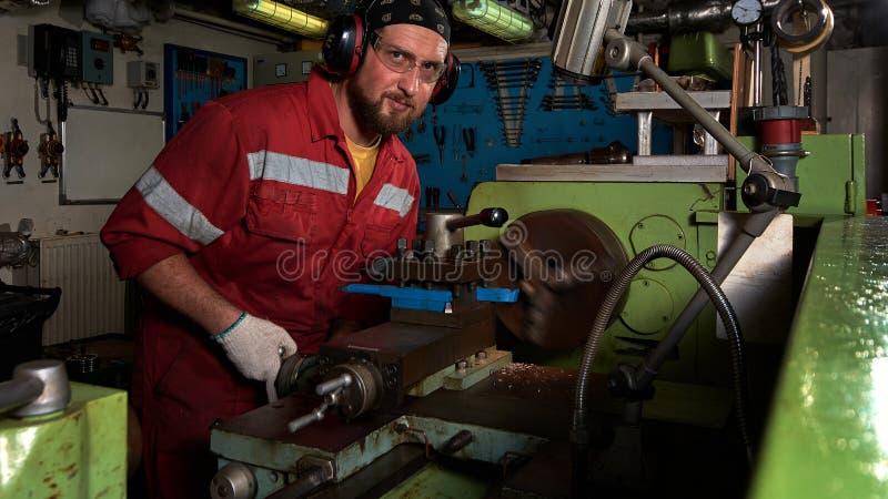 Arbeitskraft in der roten Uniform, die in der manuellen Drehbank in der Metallgroßen Werkstatt funktioniert stockfoto
